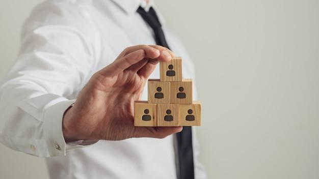 Ejecutivo de negocios que sostiene cubos de madera con el icono de persona en ellos construido en una estructura piramidal. imagen conceptual del empleo y los recursos humanos.