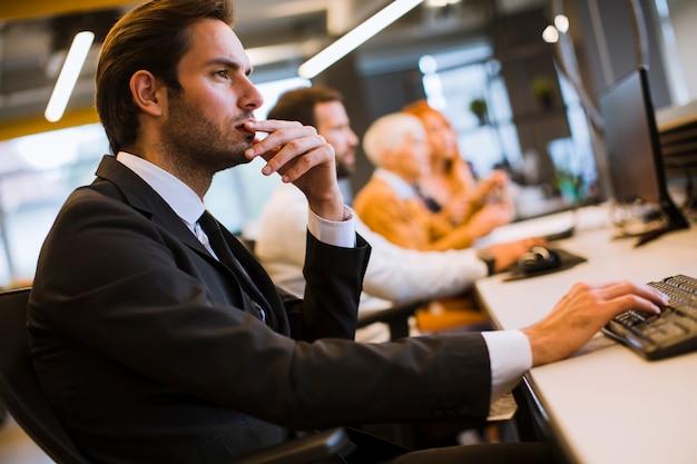 Ejecutivo de negocios en reunión de grupo con otros empresarios y empresarias en la oficina moderna con computadora