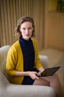 Ejecutivo de negocios seguro sentado con tableta digital en el sofá