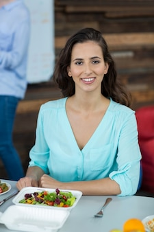 Ejecutivo de negocios sonriente que tiene comida en oficina