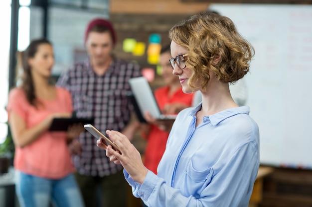 Ejecutivo de negocios mediante teléfono móvil en la oficina