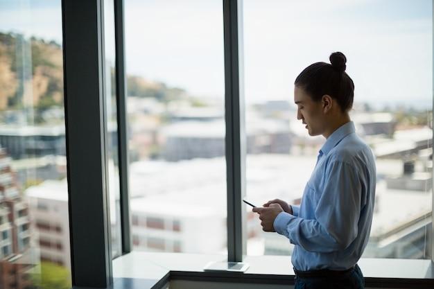 Ejecutivo de negocios mediante teléfono móvil en el pasillo