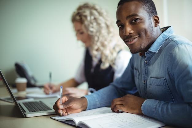 Ejecutivo de negocios tomando notas mientras usa la computadora portátil