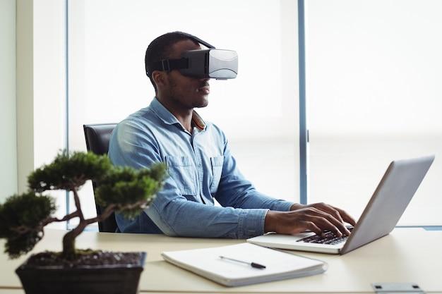 Ejecutivo de negocios usando casco de realidad virtual y trabajando en una computadora portátil