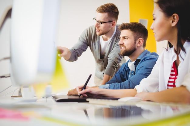 Ejecutivo señalando el monitor de la computadora a colegas en la oficina creativa