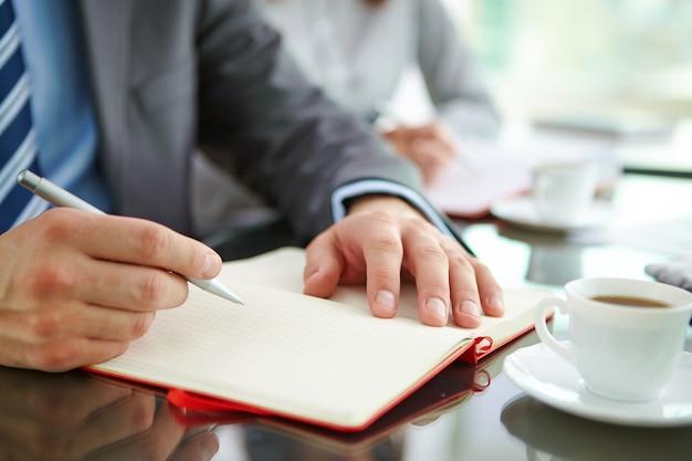 Ejecutivo de sexo masculino por escrito en el cuaderno abierto