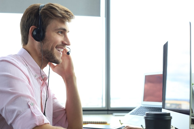 Ejecutivo de soporte al cliente masculino joven feliz que trabaja en la oficina.