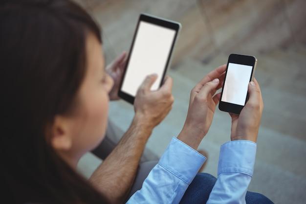 Ejecutivo mediante teléfono móvil y tableta digital