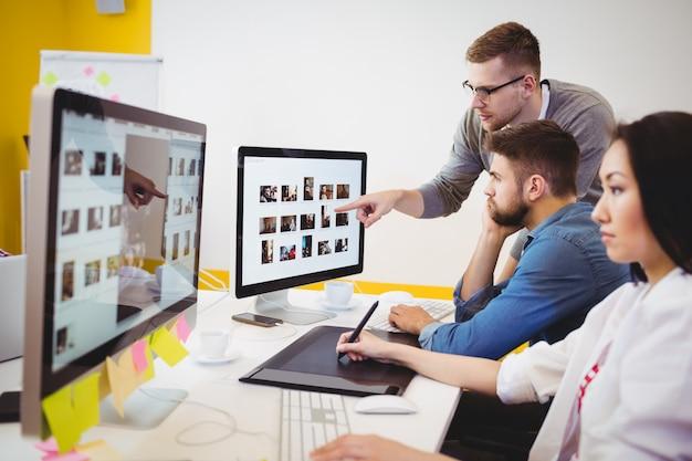 Ejecutivo usando tableta gráfica mientras colegas discutían en la oficina creativa