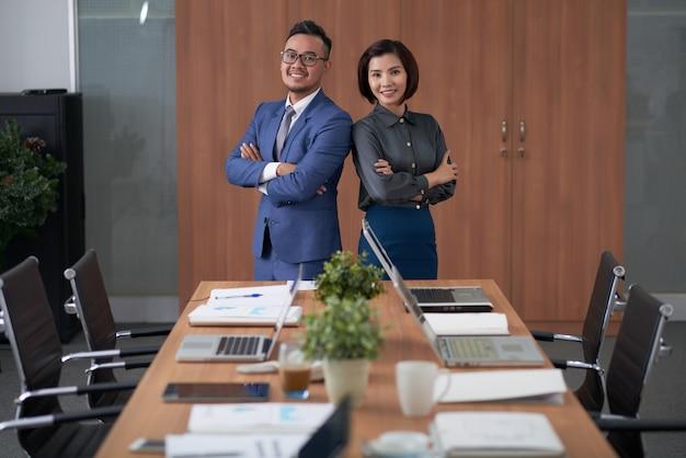 Ejecutivos asiáticos masculinos y femeninos posando en la parte superior de la mesa de reuniones en la sala de juntas
