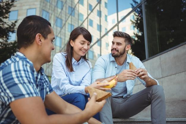 Ejecutivos desayunando fuera del edificio de oficinas