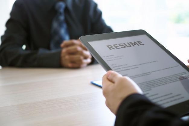 Los ejecutivos están entrevistando y viendo el currículum a través de una tableta.