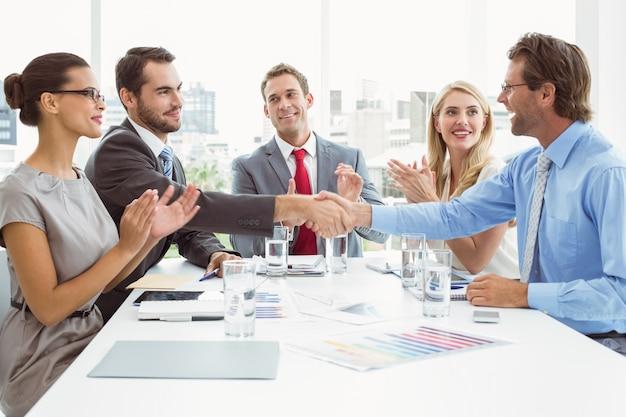 Ejecutivos estrechándose la mano en la reunión de la sala de juntas