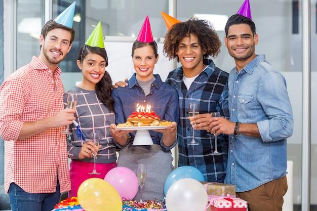 Ejecutivos felices celebrando el cumpleaños de sus colegas