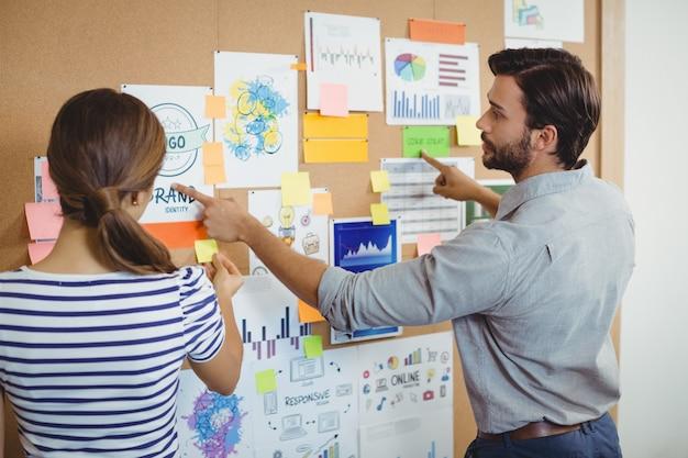 Ejecutivos masculinos y femeninos discutiendo sobre el tablón de anuncios