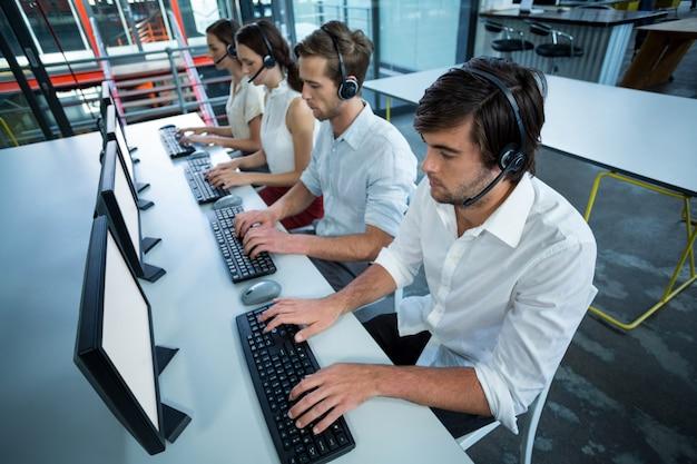 Ejecutivos de negocios con auriculares usando computadora