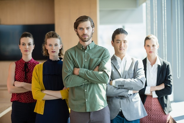 Ejecutivos de negocios con los brazos cruzados de pie en la oficina