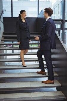 Ejecutivos de negocios conversando en las escaleras