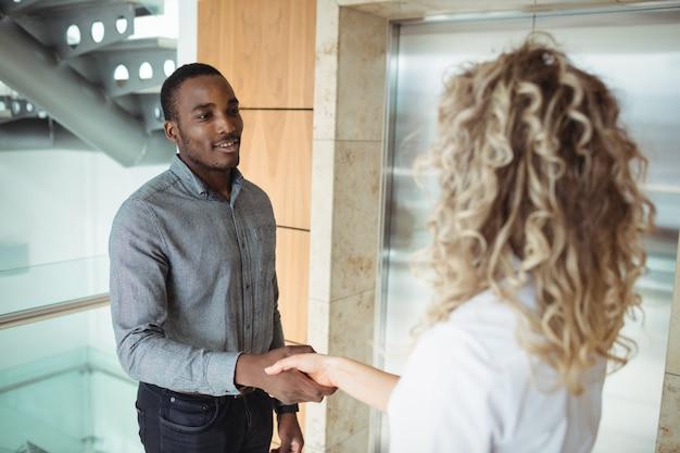 Ejecutivos de negocios dándose la mano cerca del ascensor