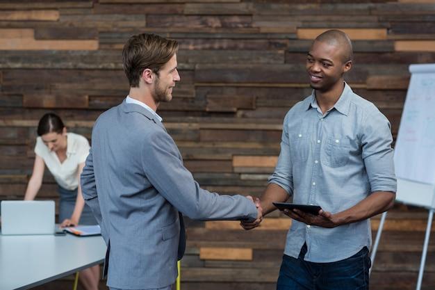 Ejecutivos de negocios dándose la mano en la oficina