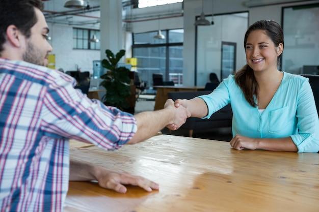 Ejecutivos de negocios dándose la mano durante la reunión en la oficina