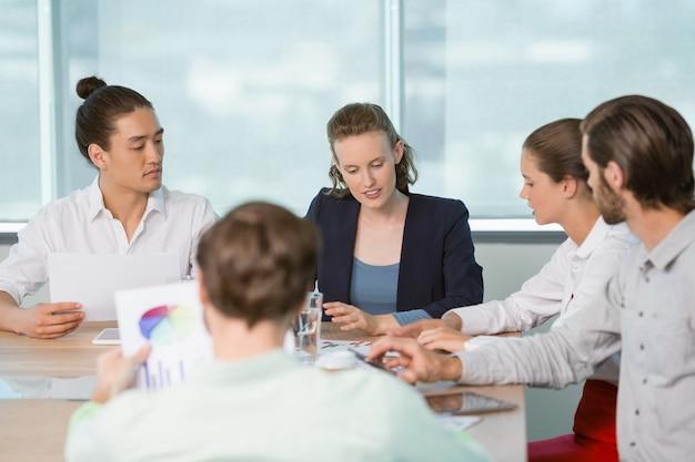 Ejecutivos de negocios discutiendo entre sí en la sala de conferencias