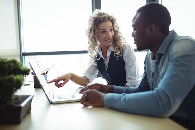 Ejecutivos de negocios discutiendo sobre laptop
