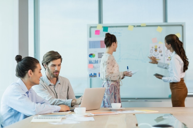 Ejecutivos de negocios discutiendo sobre un portátil en la sala de conferencias