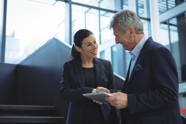 Ejecutivos de negocios discutiendo sobre tableta digital en escaleras