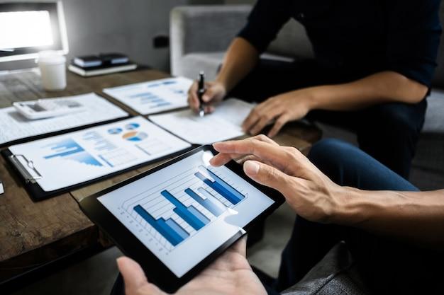 Los ejecutivos de negocios inteligentes se asocian analizando la valoración en una tableta digital y papel de datos