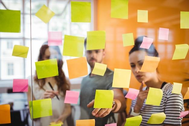 Los ejecutivos de negocios la lectura de las notas adhesivas