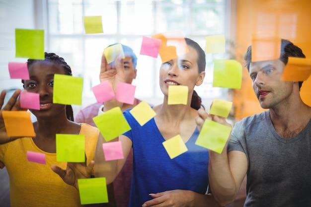 Los ejecutivos de negocios que sobresalen notas adhesivas