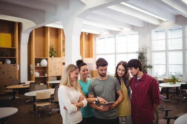 Los ejecutivos de negocios que tiene la discusión sobre la tableta digital