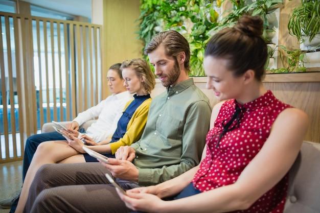 Ejecutivos de negocios que usan dispositivos electrónicos mientras están sentados