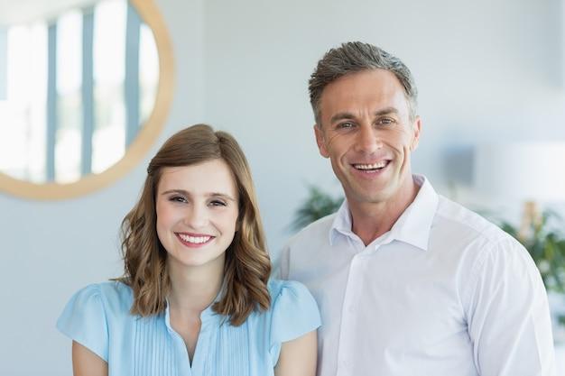 Ejecutivos de negocios sonriendo mientras está de pie en la oficina