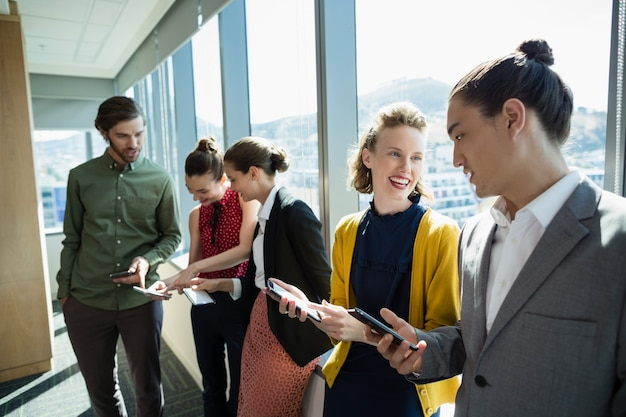 Ejecutivos de negocios sonriendo mientras usan dispositivos electrónicos