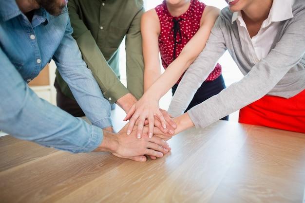 Ejecutivos de negocios con sus manos apiladas sobre la mesa de madera