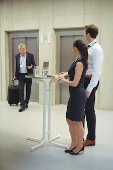 Ejecutivos de pie con vasos de agua para dar la bienvenida a su colega