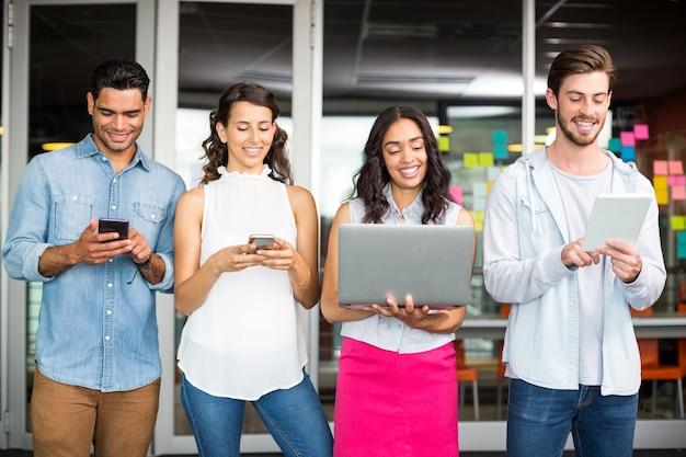 Ejecutivos sonrientes mediante teléfono móvil, computadora portátil y tableta digital