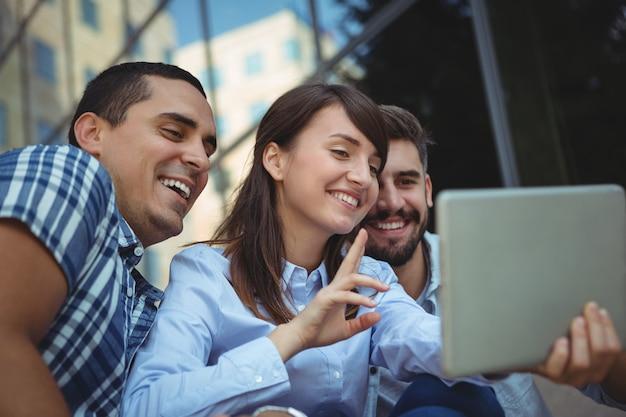 Ejecutivos mediante tableta digital fuera del edificio de oficinas