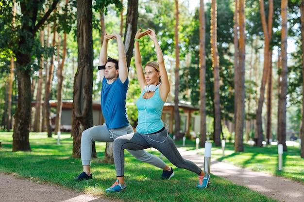 Ejercicio al aire libre. gente agradable positiva haciendo ejercicio mientras está en el parque