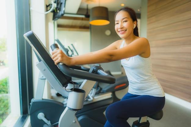 El ejercicio asiático de la mujer del deporte joven hermoso del retrato y se resuelve con el equipo de la aptitud en gimnasio
