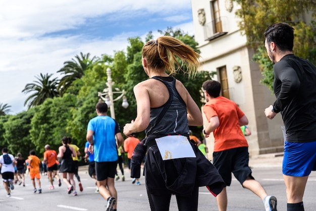 Ejercicio bastante corriente de la chica joven bastante rubia en una raza corriente rodeada por otros corredores.