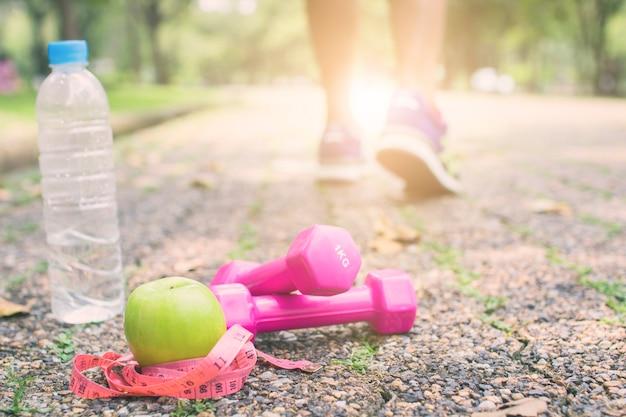El ejercicio y el concepto de dieta fitness, pesa de gimnasia con manzana verde y agua en el camino del deporte
