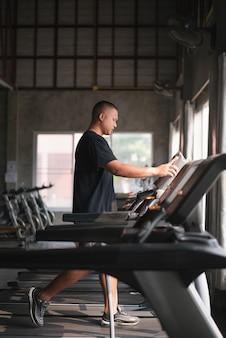 Ejercicio de deporte hombre usando caminar en la cinta en el gimnasio