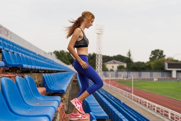 Ejercicio de escaleras en el estadio con mujer joven