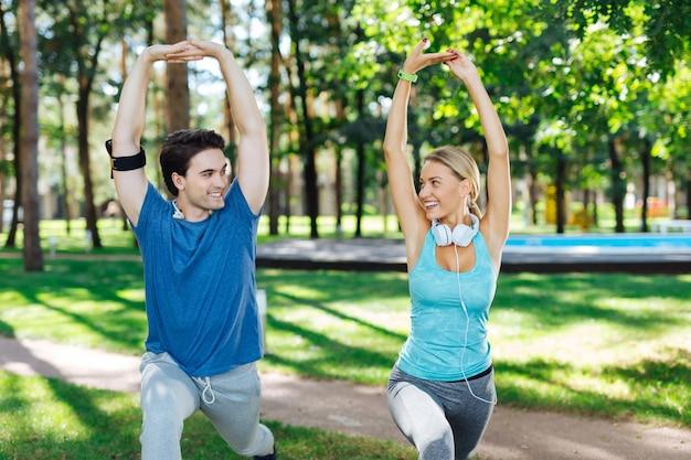 Ejercicio físico. pareja positiva alegre sosteniendo sus manos mientras hace ejercicio físico