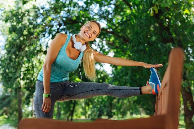 Ejercicio de flexibilidad. mujer alegre y encantada que le sonríe mientras hace un ejercicio de flexibilidad