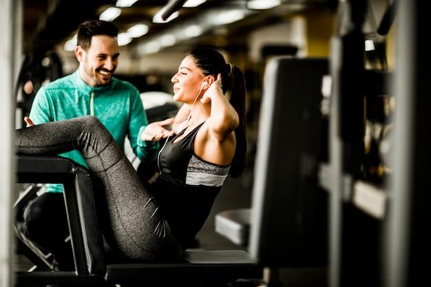 Ejercicio de mujer joven con la ayuda del entrenador en el gimnasio