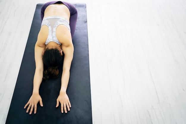 Ejercicio de mujer joven deporte con pose de yoga en el club deportivo